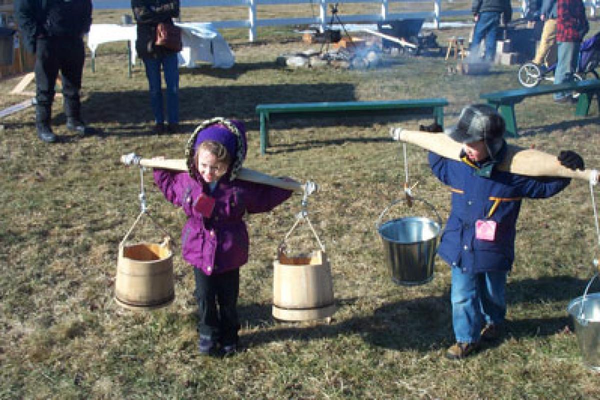 Children balancing buckets